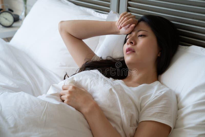 De zieke vrouw lijdt aan hoofdpijn met hand op voorhoofd royalty-vrije stock afbeeldingen
