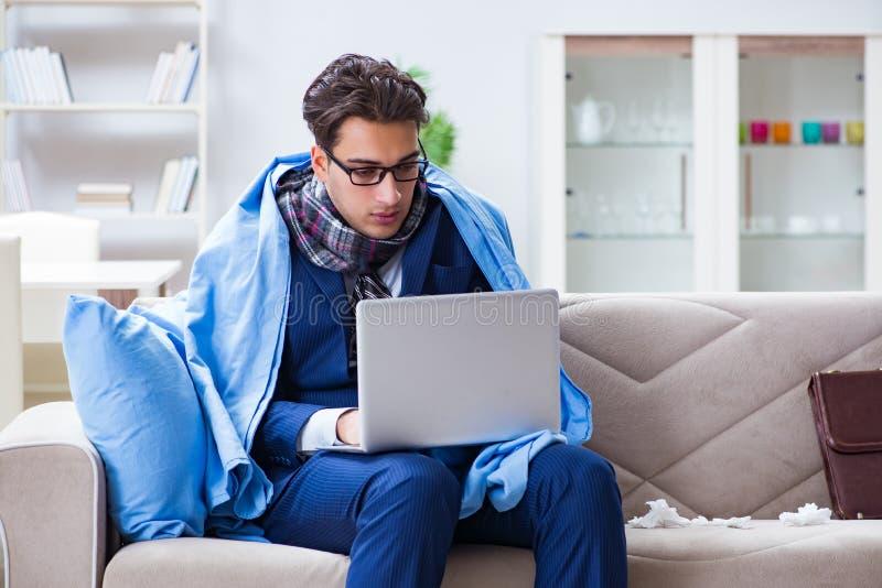 De zieke zakenman die van huis toe te schrijven aan griepziekte werken stock foto's