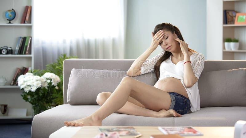 De zieken moeder-aan-raken voorhoofd controlerend lichaamstemperatuur die aan hoofdpijn lijden stock afbeelding