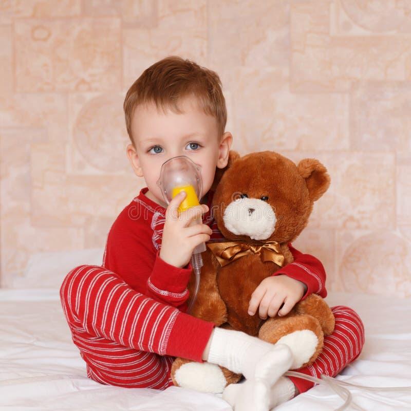 De zieken weinig jongen maakt inhalatiemasker voor thuis ademhaling stock foto
