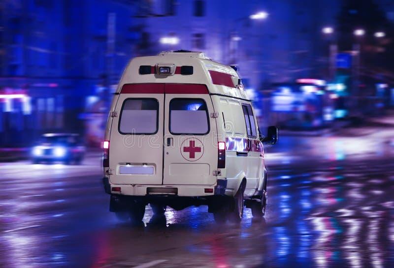 De ziekenwagen gaat op nachtstad stock afbeeldingen