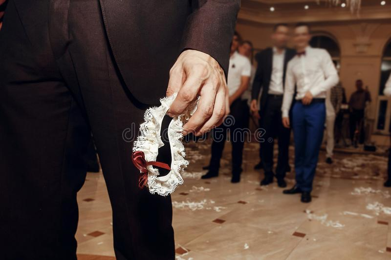De zijdekouseband van de bruidegomholding van bruid bij huwelijkspartij traditie royalty-vrije stock afbeeldingen