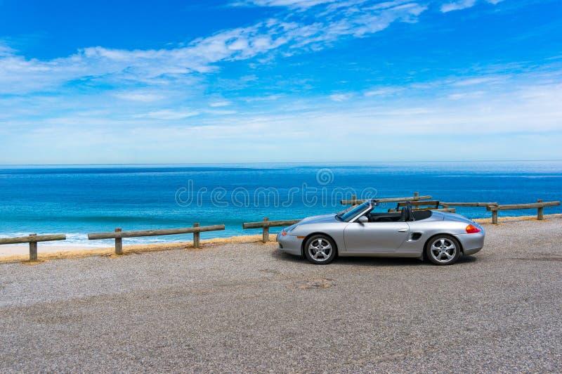 De zilveren convertibele auto van Porsche met oceaan op de achtergrond royalty-vrije stock fotografie