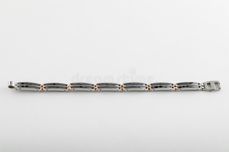De zilveren glanzende armband van mensen met zwarte steentussenvoegsels en gouden die verbindingen op witte achtergrond worden ge stock afbeeldingen