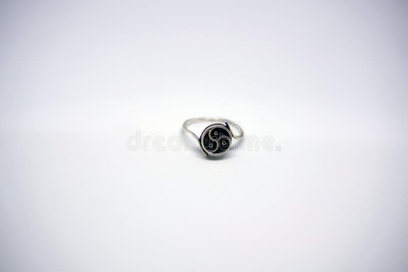 De zilveren ring met bdsmsymbool Triskel ligt op een witte achtergrond in de Studio stock foto