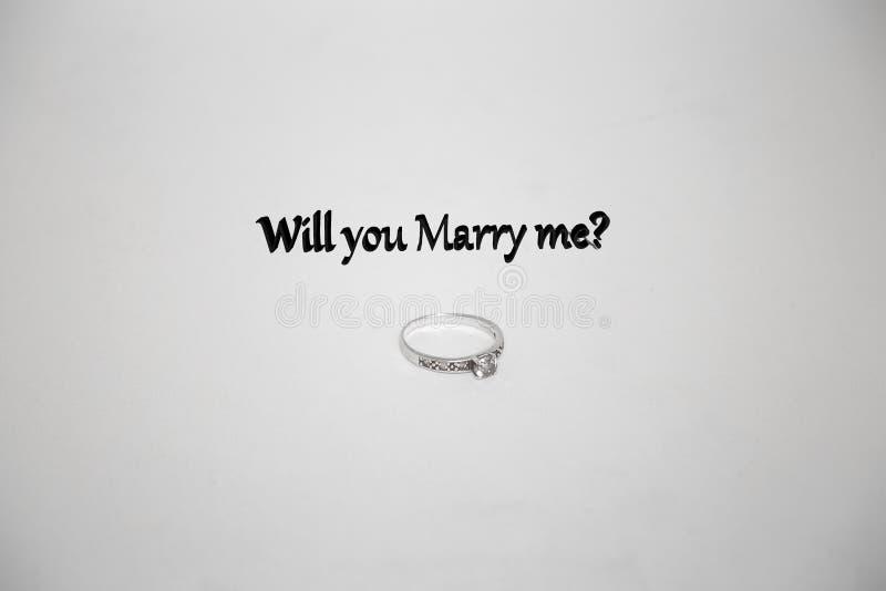 De zilveren verlovingsringen met de tekst zullen u me huwen stock fotografie