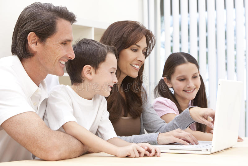 De Zitting die van de familie Laptop Computer thuis met behulp van stock afbeeldingen