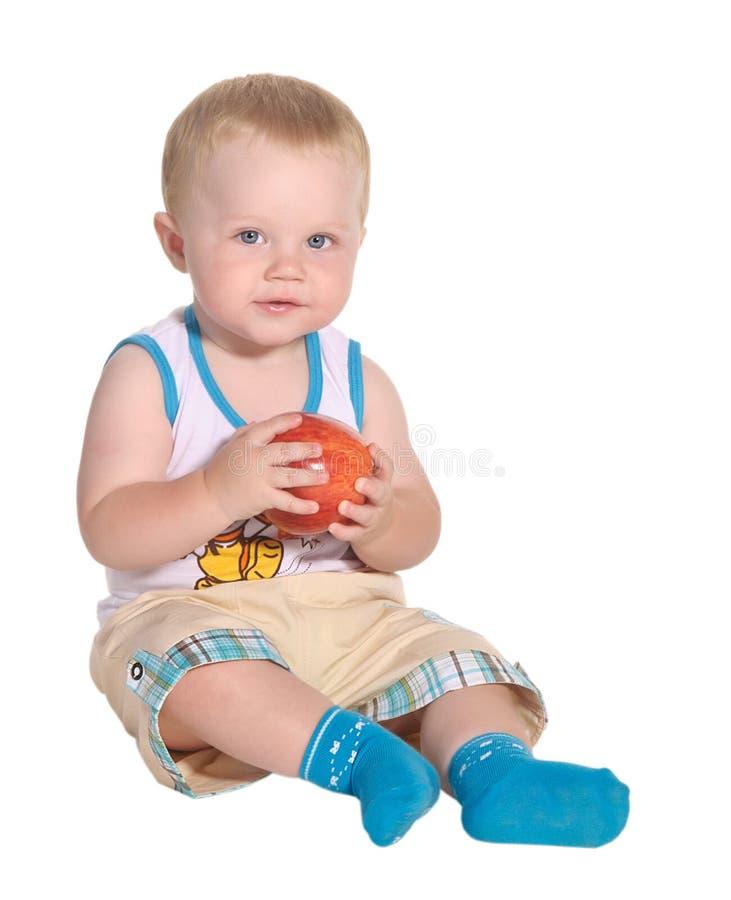 De zitting en de holding van de baby een appel royalty-vrije stock foto's