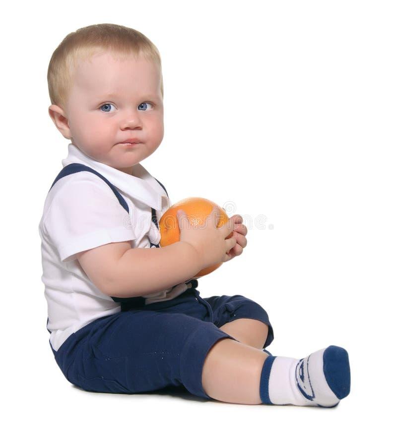 De zitting en de holding van de baby een sinaasappel stock afbeelding