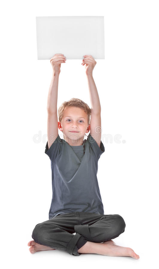 De zitting en de holding van de jongen een lege witte pagina stock foto