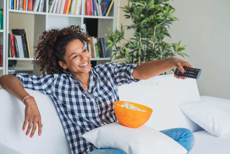 De zitting van de Afrovrouw thuis met afstandsbediening die op TV letten royalty-vrije stock foto