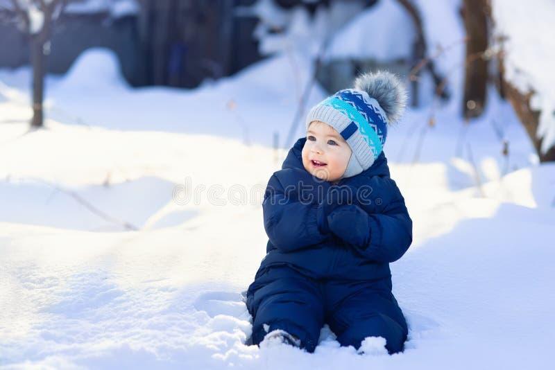 De zitting van de babyjongen op sneeuw royalty-vrije stock afbeeldingen