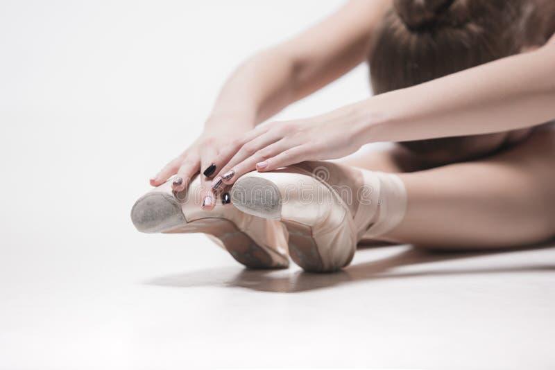 De zitting van de ballerinadanser neer met haar gekruiste benen stock afbeeldingen