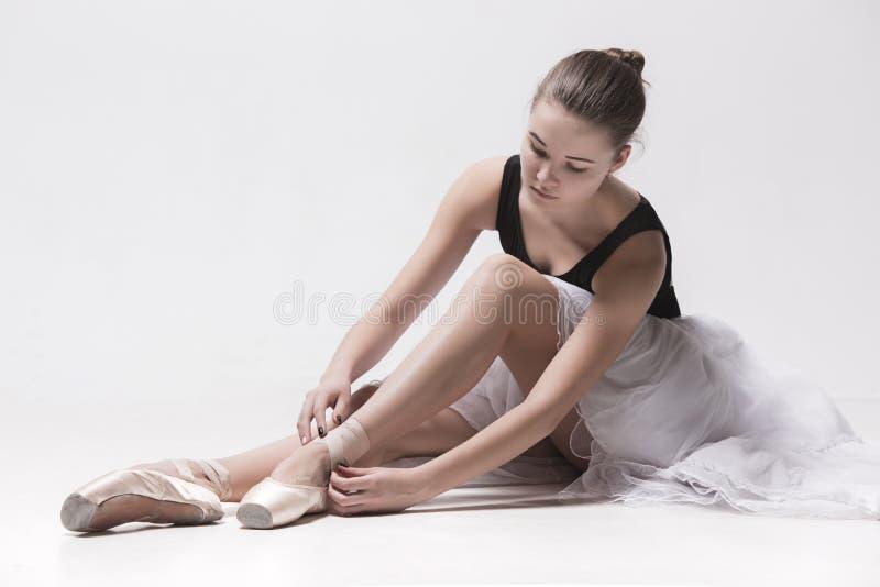 De zitting van de ballerinadanser neer met haar gekruiste benen royalty-vrije stock afbeeldingen