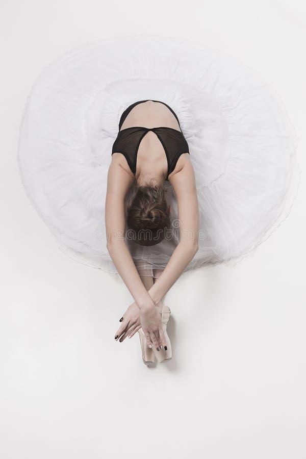 De zitting van de ballerinadanser neer met haar gekruiste benen royalty-vrije stock afbeelding