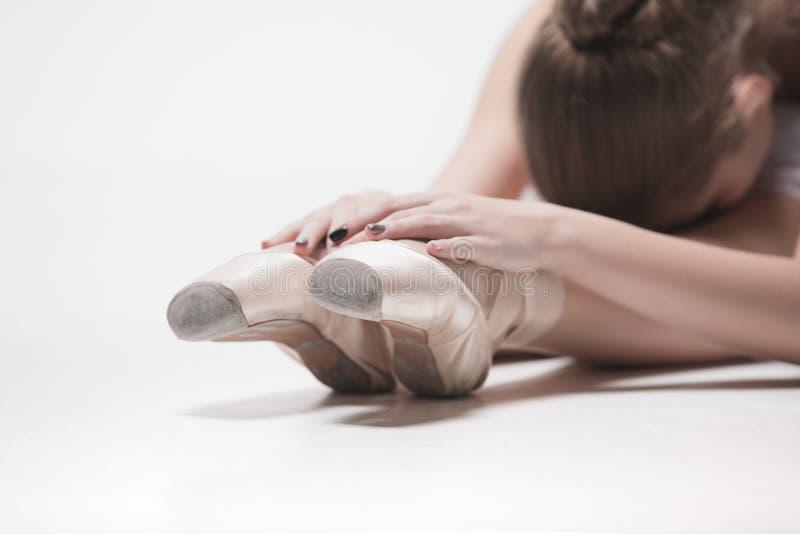 De zitting van de ballerinadanser neer met haar gekruiste benen royalty-vrije stock fotografie