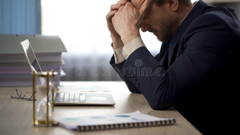 De zitting van de bedrijfarbeider bij bureau, die tempels, vermoeidheid wrijven, overwerk royalty-vrije stock foto