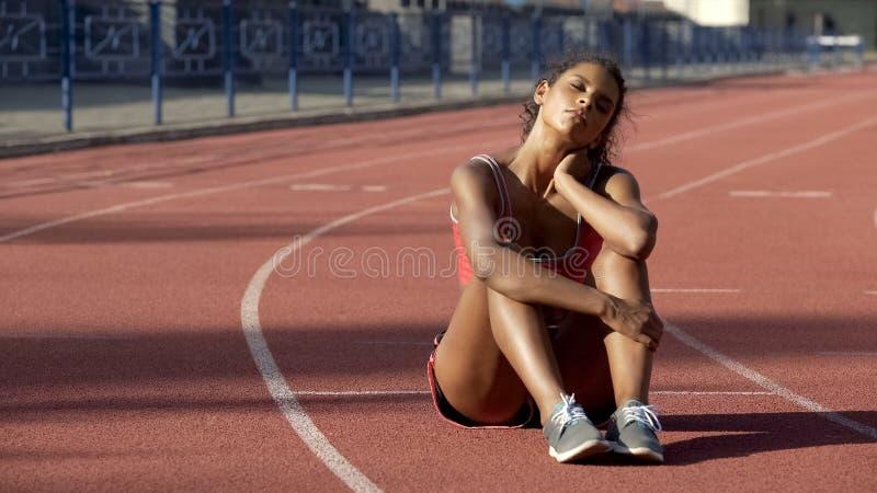 De zitting van de Biracialsportvrouw vermoeide na opleiding in uitgeput midden van spoor, stock foto