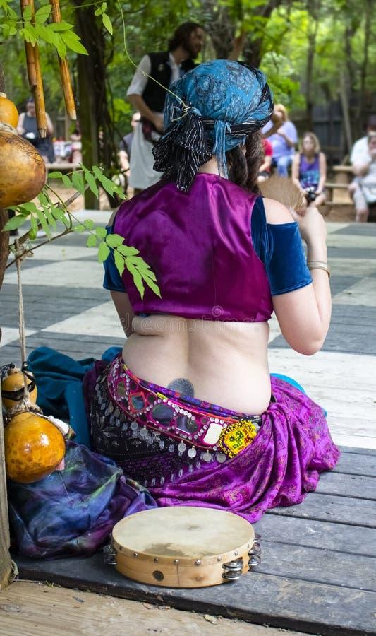 De zitting van de buikdanser aan de kant van het houten openluchtstadium na het dansen met haar tamborine naast haar die waaien i stock foto