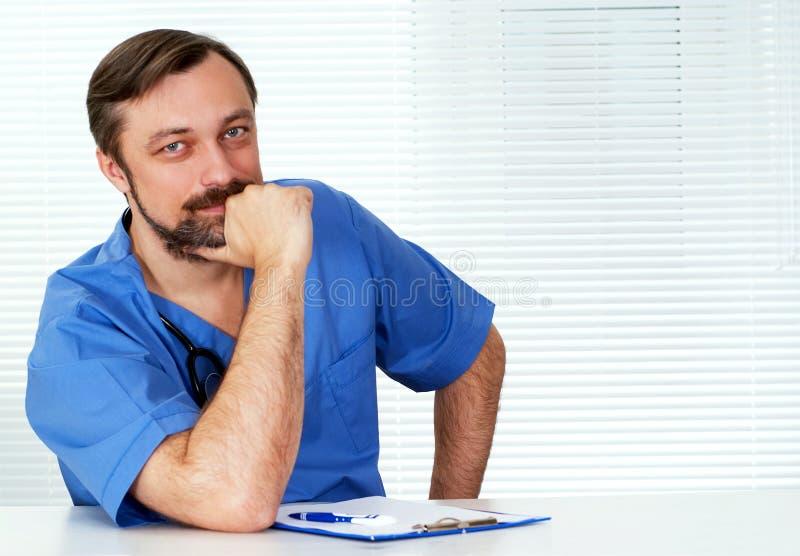 De zitting van de arts op het wit stock foto's