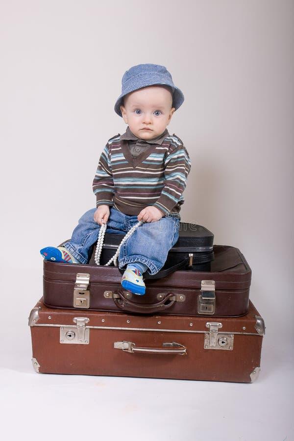 De zitting van de baby in een oude koffer stock afbeelding