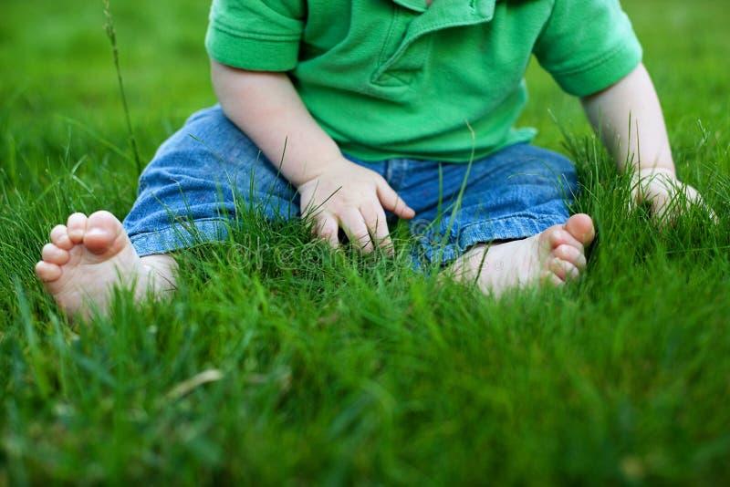 De zitting van de baby in het gras stock foto