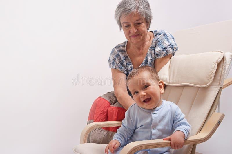 De zitting van de baby op stoel en het lachen met grootmoeder royalty-vrije stock afbeelding