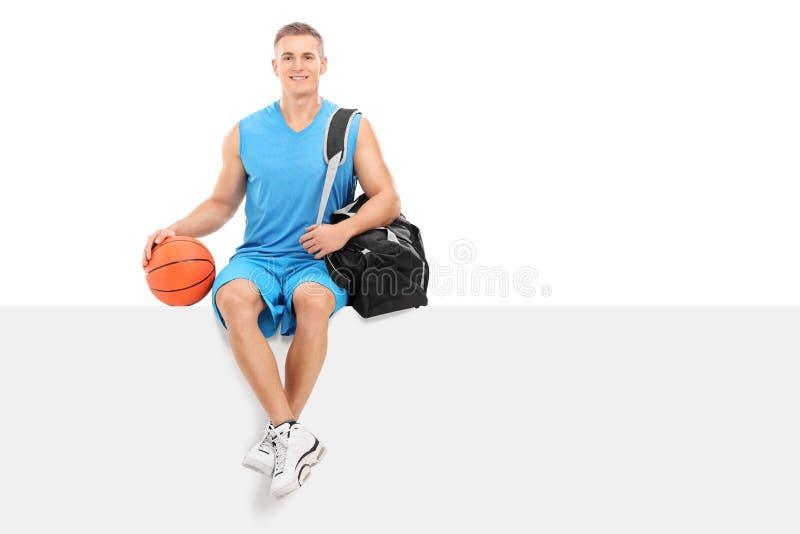 De zitting van de basketbalspeler op een leeg paneel royalty-vrije stock foto's