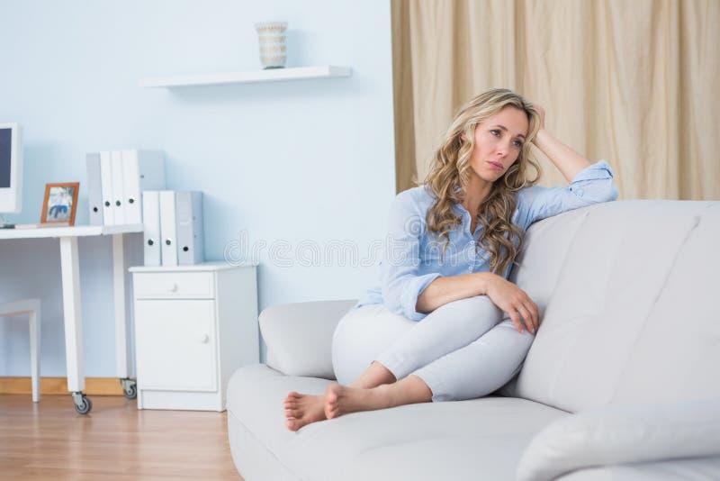 De zitting van de blondevrouw bij laag het denken stock foto