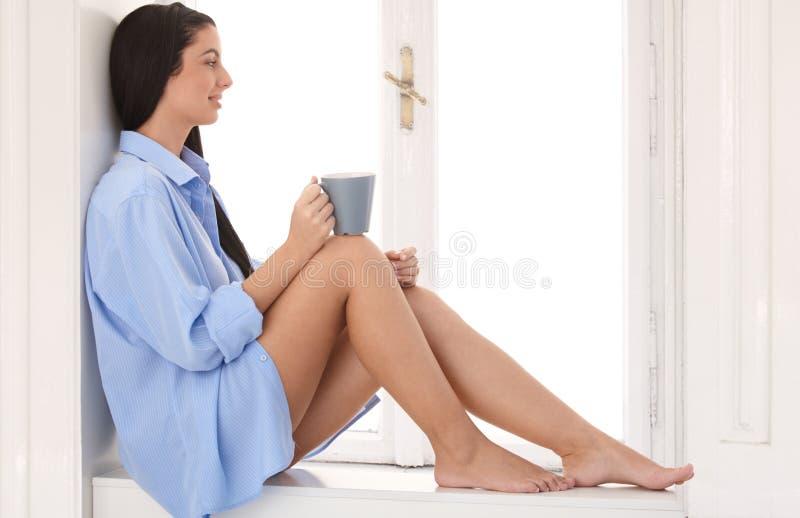 De zitting van de dagdromenvrouw bij venstervensterbank stock foto's