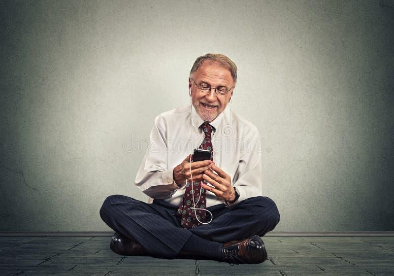 De zitting van de de hogere uitvoerende machtmens op een vloer die slimme telefoon texting het luisteren muziek gebruiken royalty-vrije stock fotografie