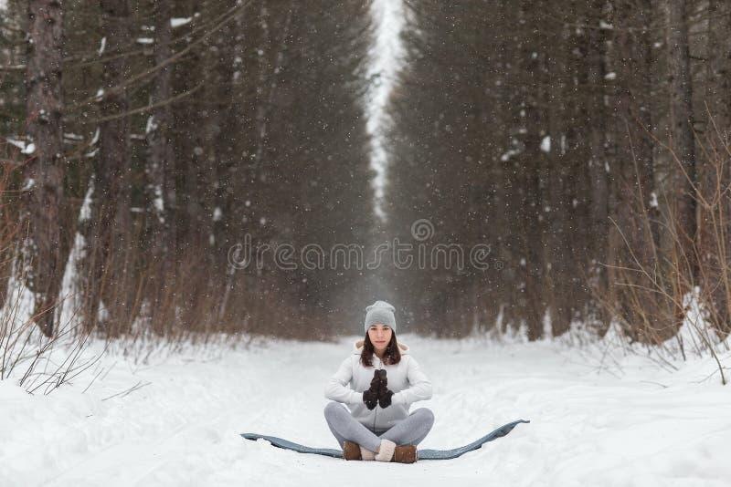 De zitting van de de winteryoga in mooie plaats royalty-vrije stock afbeelding