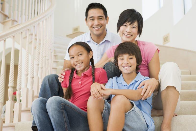 De zitting van de familie bij trap het glimlachen