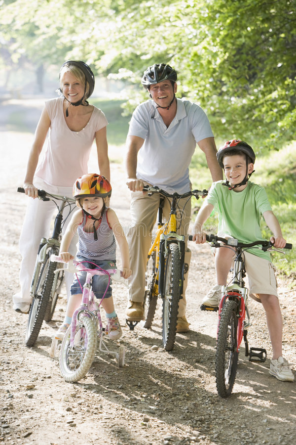 De zitting van de familie op fietsen bij weg het glimlachen stock afbeelding
