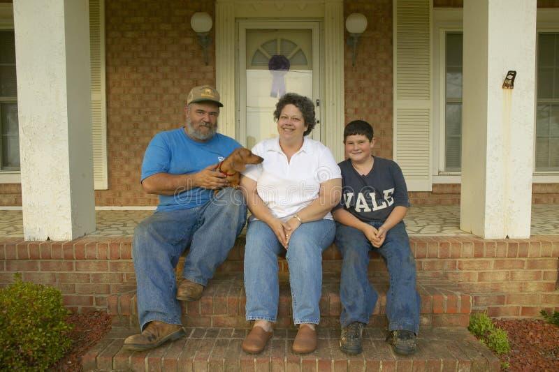 De zitting van de familie op voorportiek van huis stock afbeelding