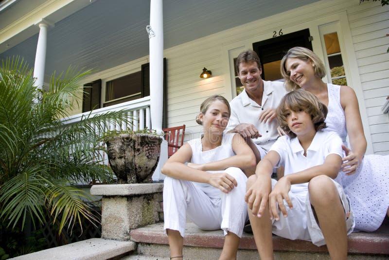 De zitting van de familie samen op voorportiekstappen royalty-vrije stock foto