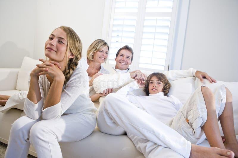 De zitting van de familie samen op witte bank die op TV let stock foto's