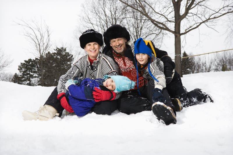 De zitting van de familie in sneeuw. royalty-vrije stock foto's