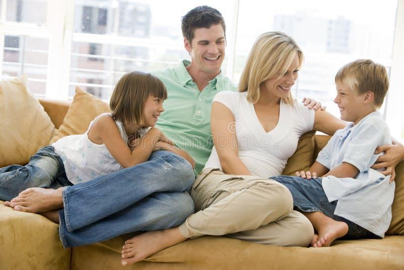 De zitting van de familie in woonkamer het glimlachen royalty-vrije stock afbeelding