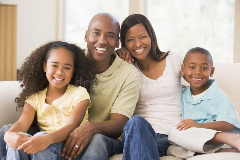 De zitting van de familie in woonkamer het glimlachen stock foto