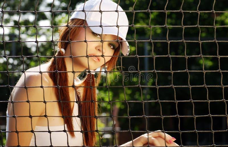 De zitting van de het tennisspeler van de vrouw achter het net stock afbeeldingen