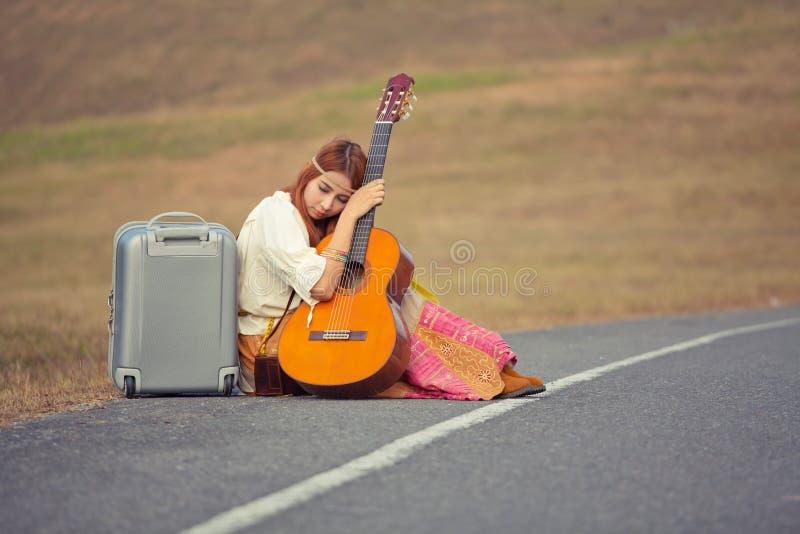 De zitting van de hippievrouw op een plattelandsweg stock afbeeldingen