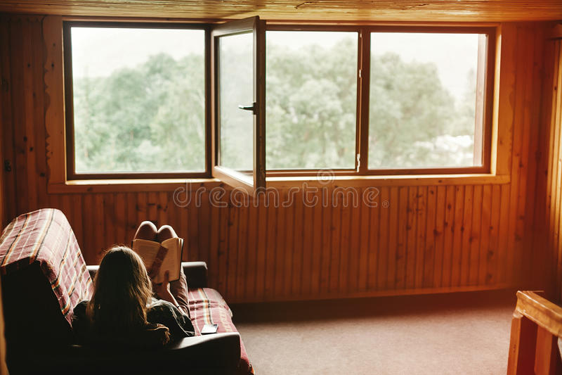 De zitting van de Hipstervrouw op bus en lezingsboek in houten cottag royalty-vrije stock afbeelding