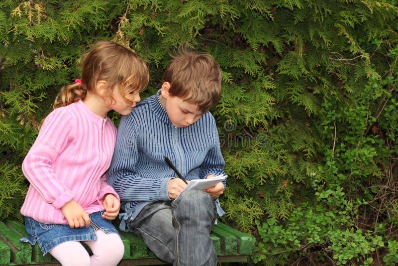 De zitting van de jongen en van het meisje op bank dichtbij bomen stock foto's