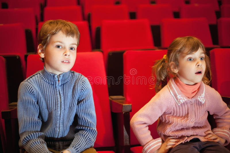 De zitting van de jongen en van het meisje op leunstoelen bij bioskoop royalty-vrije stock afbeelding