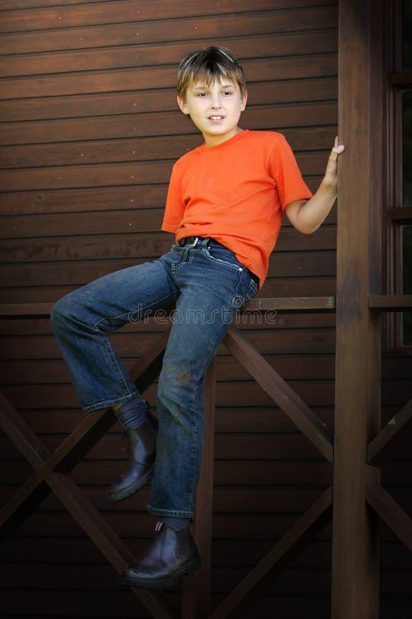De zitting van de jongen op de veranda royalty-vrije stock fotografie