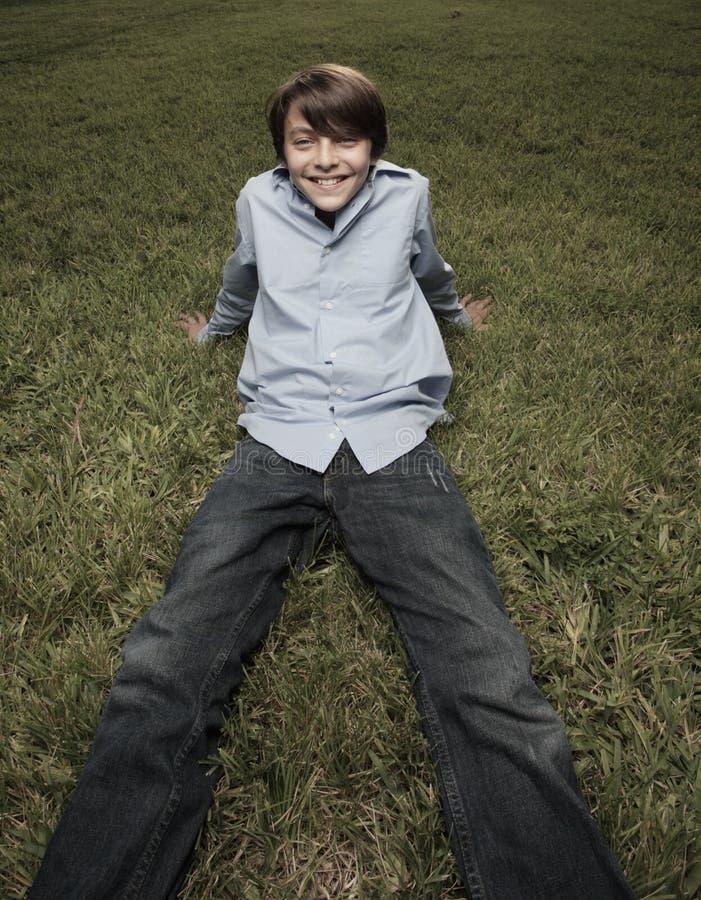 De zitting van de jongen op het gras royalty-vrije stock afbeeldingen