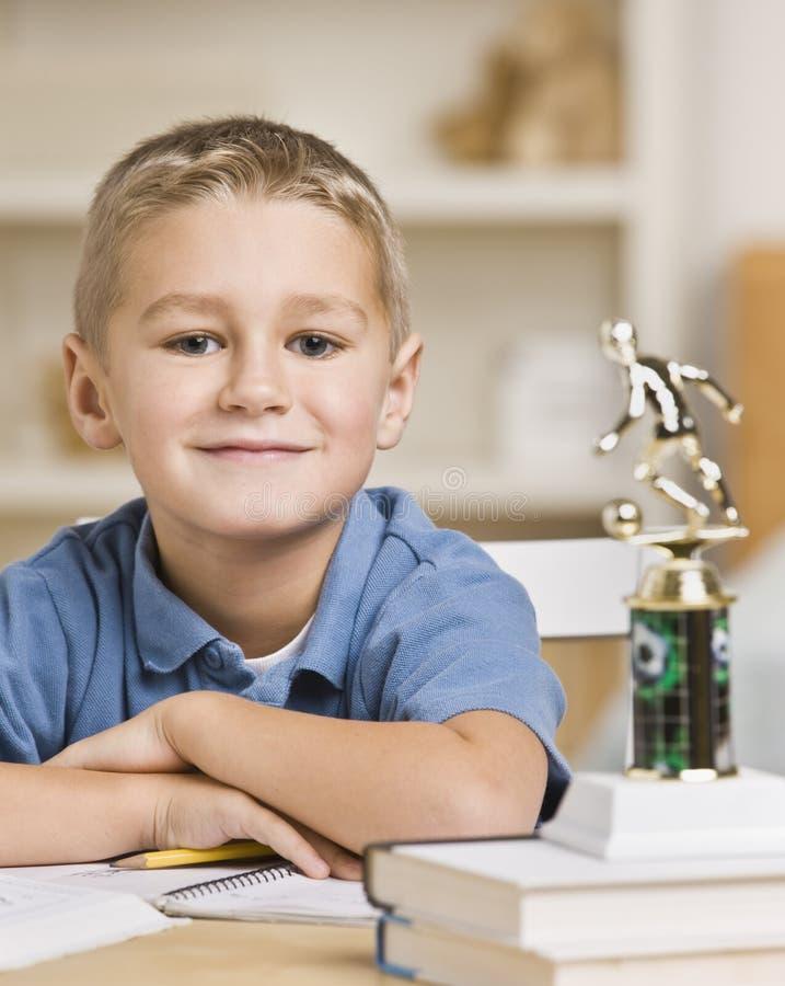 De Zitting van de jongen voor de Trofee van het Voetbal stock afbeelding