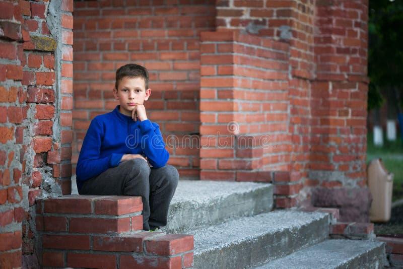 De zitting van de jongenstiener op portiek thuis royalty-vrije stock afbeelding