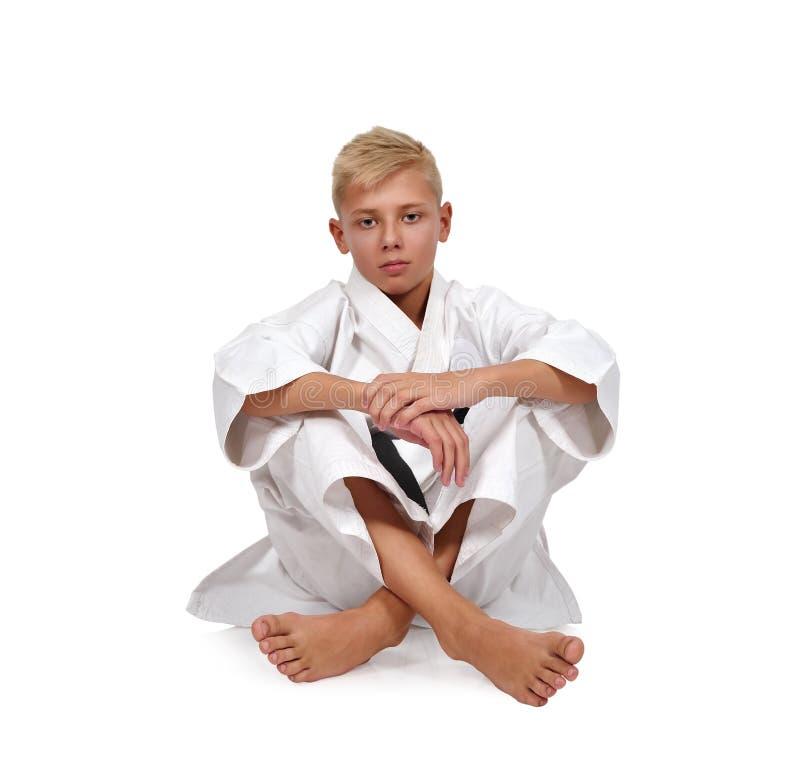 De zitting van de karatejongen op vloer royalty-vrije stock foto's